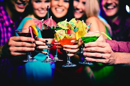 personas festejando: Gafas con cócteles en poder de los amigos felices en la fiesta