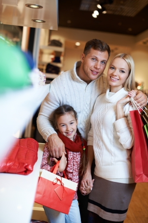 Portrait of young couple and their daughter looking at camera in the mall photo