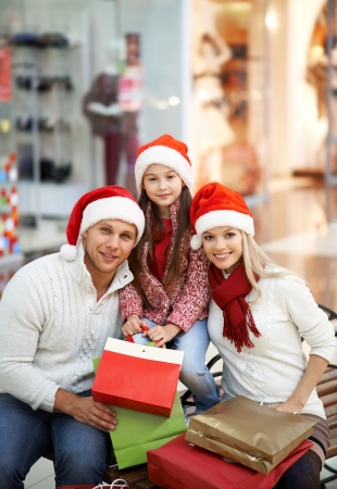 Portrait of young couple and their daughter in Santa caps sitting in the mall photo