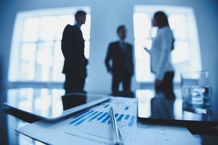 papeles oficina: Primer plano de documento de negocios y touchpads en lugar de trabajo en el fondo de los trabajadores de oficina interactuando Foto de archivo