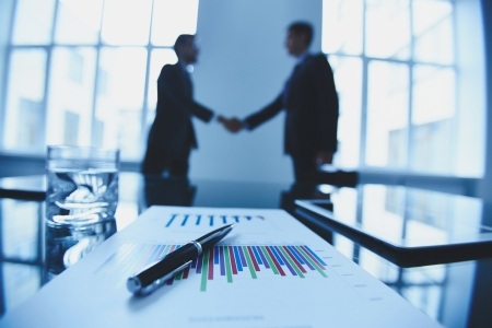handshaking: Close-up of business objects at workplace on background of partners handshaking Stock Photo