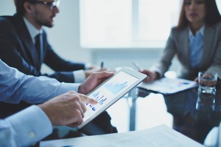 ejecutivo en oficina: Imagen de hombre de negocios que se�ala en el documento en el touchpad en la reuni�n Foto de archivo
