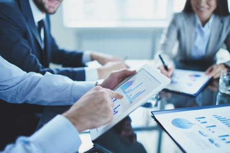 tecnología: Imagen de hombre de negocios apuntando al documento en el touchpad en la reunión