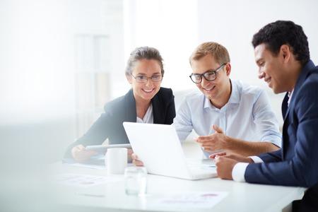 Retrato de socios de negocios inteligentes usando la computadora portátil en el cumplimiento de