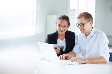 using laptop: Portrait of businessman and businesswoman looking at laptop display at meeting