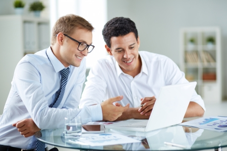 competitive business: Portrait of smart businessmen discussing project in laptop at meeting Stock Photo