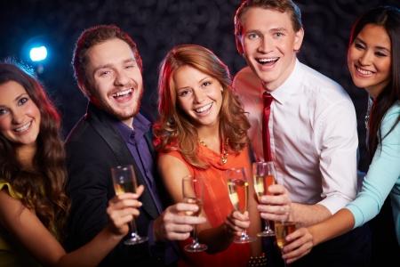 brindisi spumante: Gruppo di amici allegri brindando con champagne nel bar Archivio Fotografico