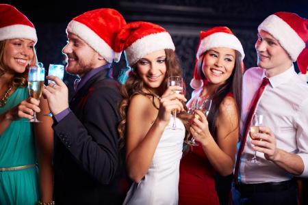 Company of friends in Santa caps holding flutes of champagne at Christmas party