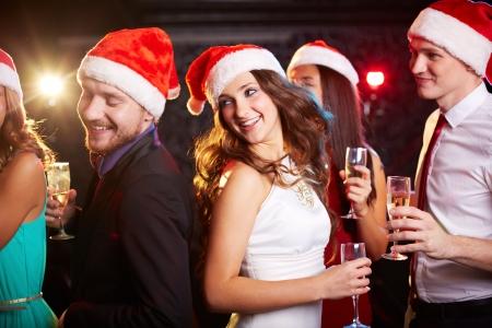 Bedrijf van vrienden in Santa caps houden fluiten champagne tijdens het dansen op kerstfeest Stockfoto