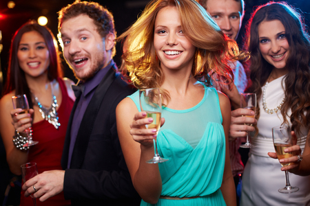 energy drinks: Portrait of cheerful girl with champagne flute dancing at party on background of her friends