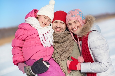 winterwear: Happy parents and their daughter in winterwear looking at camera with smiles Stock Photo