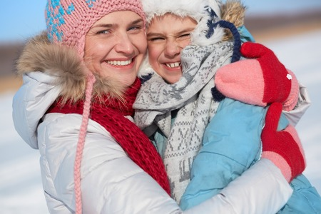 winterwear: Happy woman and her son in winterwear looking at camera