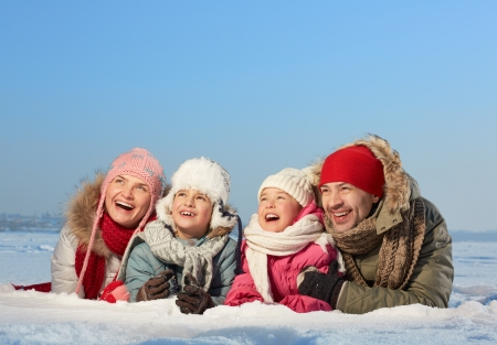 winterwear: Happy parents and their kids in winterwear lying in snow