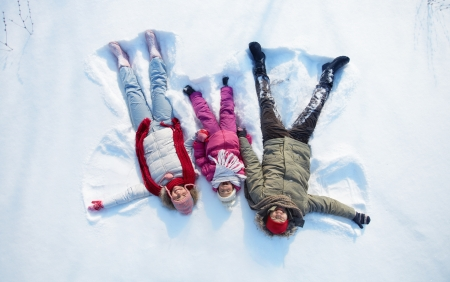 Happy parents and their daughter having fun in snowdrift