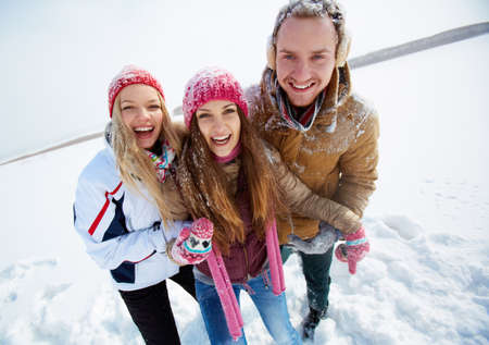 winterwear: Portrait of happy friends standing in snowdrift in winter Stock Photo