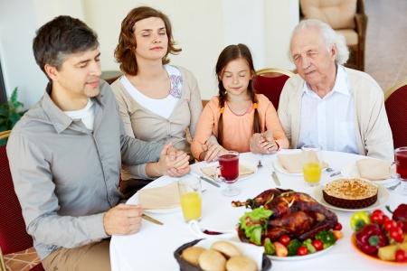 familia orando: Retrato de familia de cuatro sentados en la mesa festiva y orando