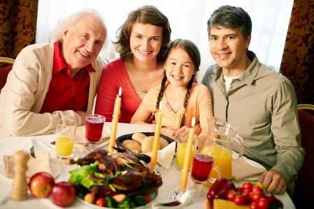 thanksgiving adult: Portrait of happy family looking at camera on holiday evening  Stock Photo