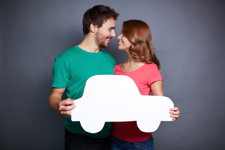 Portrait of young couple holding paper car and looking at one another photo