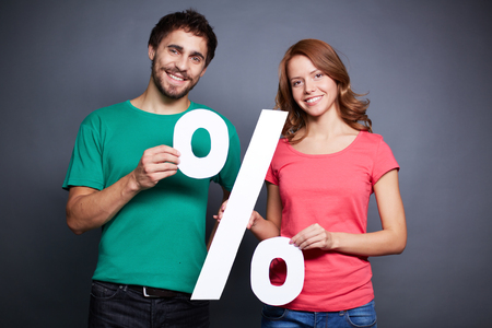 Portrait of young couple holding paper percentage sign and looking at camera photo