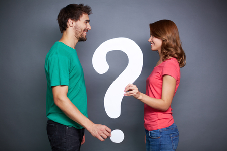 Portrait of young couple holding paper question mark and looking at on another photo