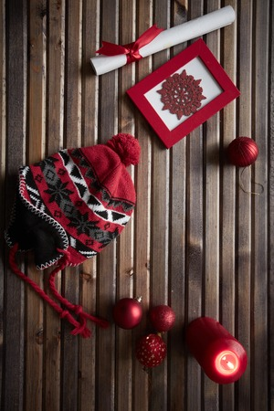 headcloth: Image of red snowflake in frame, decorative toy balls, cap, burning candle and rolled paper wrapped with red silk ribbon on wooden background
