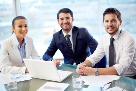 Portrait of three confident co-workers sitting in office photo