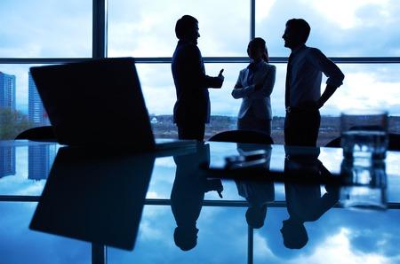 gente comunicandose: Tres oficinistas que interactúan en la ventana con su puesto de trabajo delante Foto de archivo