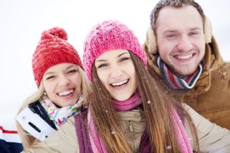 winterwear: Portrait of joyful friends looking at camera in winter with pretty girl in front Stock Photo