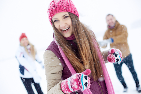 winterwear: Portrait of happy girl in winterwear laughing while playing with her friends outside