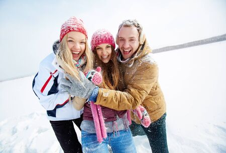 winterwear: Portrait of happy friends standing in snowdrift in winter and laughing