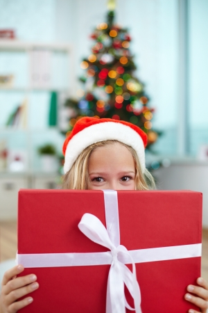 Portrait of happy girl peeking out of big red giftbox on Christmas evening