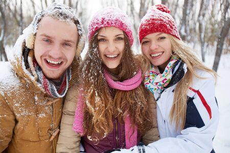 winterwear: Portrait of happy friends having fun in winter park Stock Photo