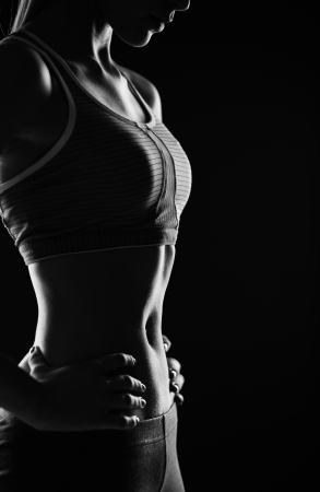 sportwear: Body of slim female in activewear standing in isolation