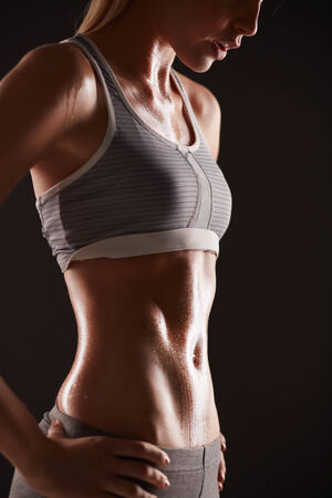 activewear: Body of slim female in activewear standing in isolation