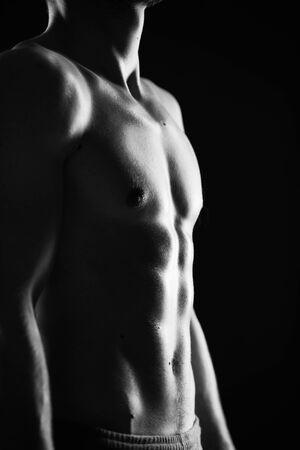 Image of bare male torso in the darkness photo