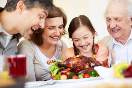 Portrait of happy family looking at appetizing roasted turkey photo