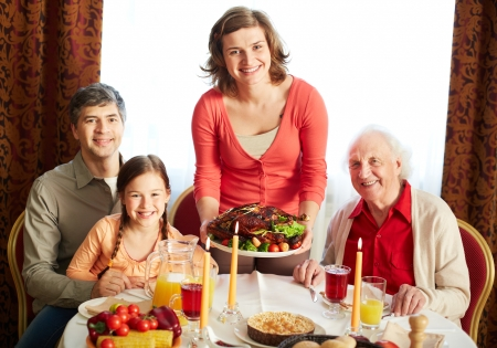 Portrait of happy family looking at camera on holiday evening  Stock Photo