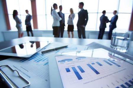 Primer plano de documento de negocios en touchpad acostado sobre la mesa, los trabajadores de oficina que interactúan en el fondo Foto de archivo - 23849316
