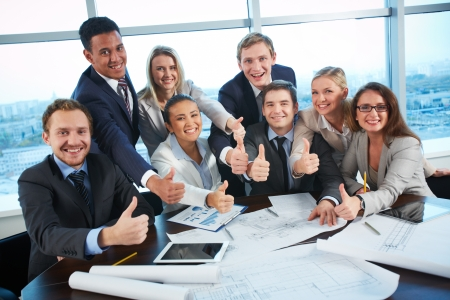 woman looking up: Group of business partners showing thumbs up while sitting at workplace in office Stock Photo