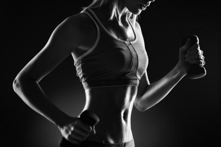 haciendo ejercicio: Cuerpo de mujer delgada en ropa deportiva haciendo ejercicio con pesas