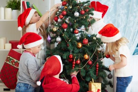 Group of adorable kids in Santa caps decorating xmas tree Stock Photo - 23849482