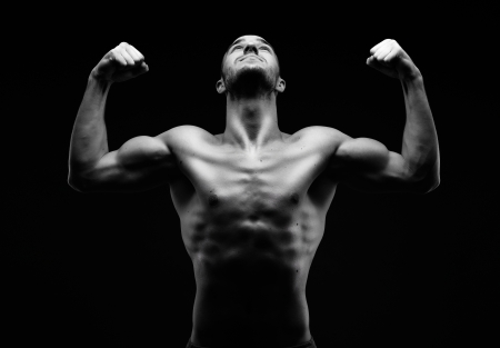 Image of shirtless man looking upwards with raised arms in front of camera photo