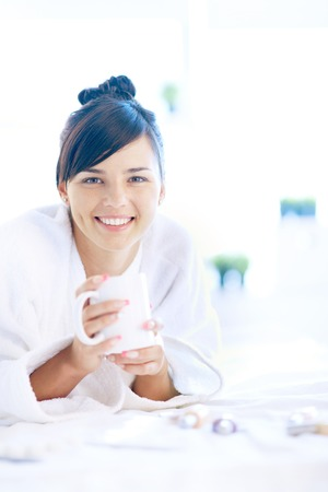 Pretty young woman in bathrobe holding cup and looking at camera photo