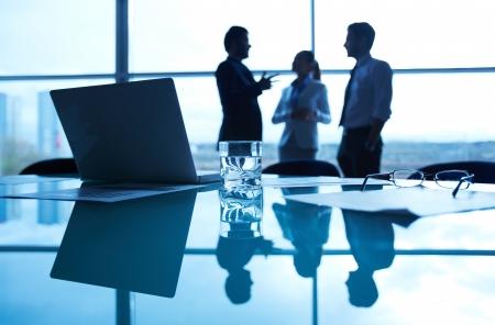 Close-up van zakelijke documenten, glas water, brillen en laptop op werk op de achtergrond van de kantoormedewerkers interactie