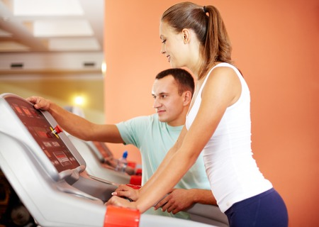 regulating: Portrait of pretty girl in gym with her trainer regulating training apparatus near by