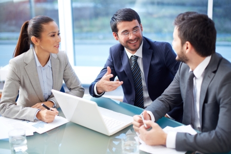 Portrait of three happy co-workers interacting at meeting in office Stock Photo