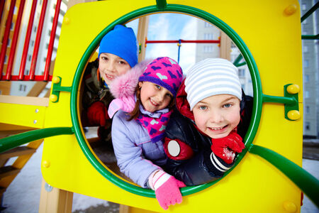 winterwear: Happy kids in winterwear looking at camera while having fun on playground