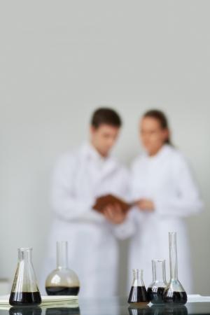 Test-tubes with liquid oil on background of two scientists working in laboratory photo