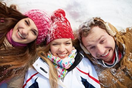 winterwear: Portrait of happy friends looking at camera in winter