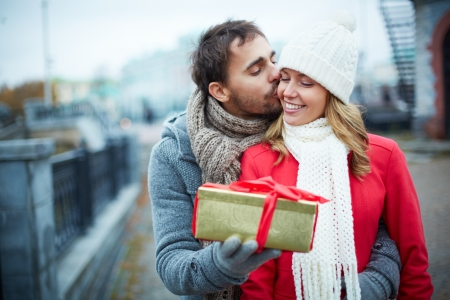 amorous woman: Image of affectionate guy kissing his girlfriend while giving her present outside